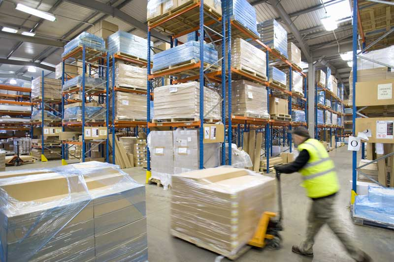 Worker moving pallets in a warehouse
