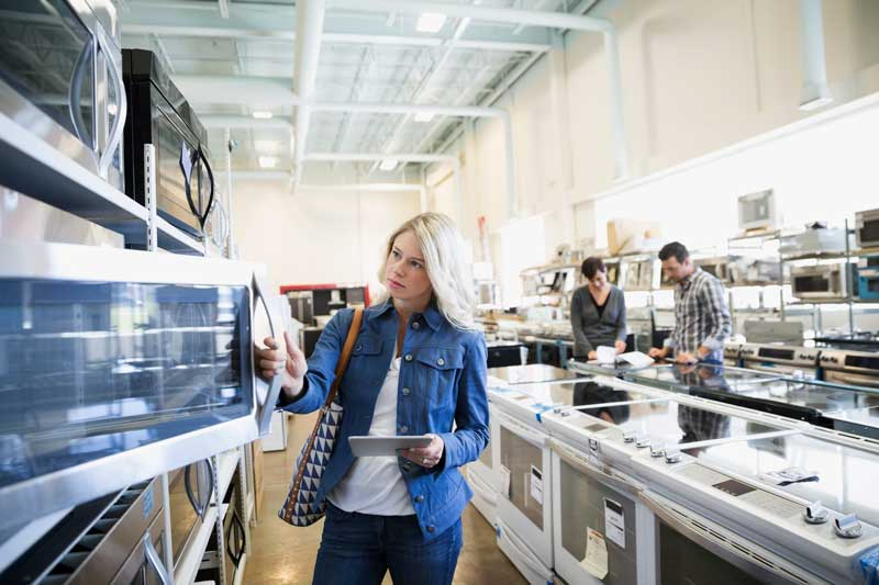 Woman looking at appliances in a showroom