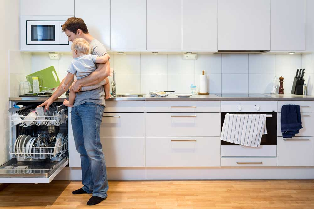 Father holding his child while stacking dishwasher